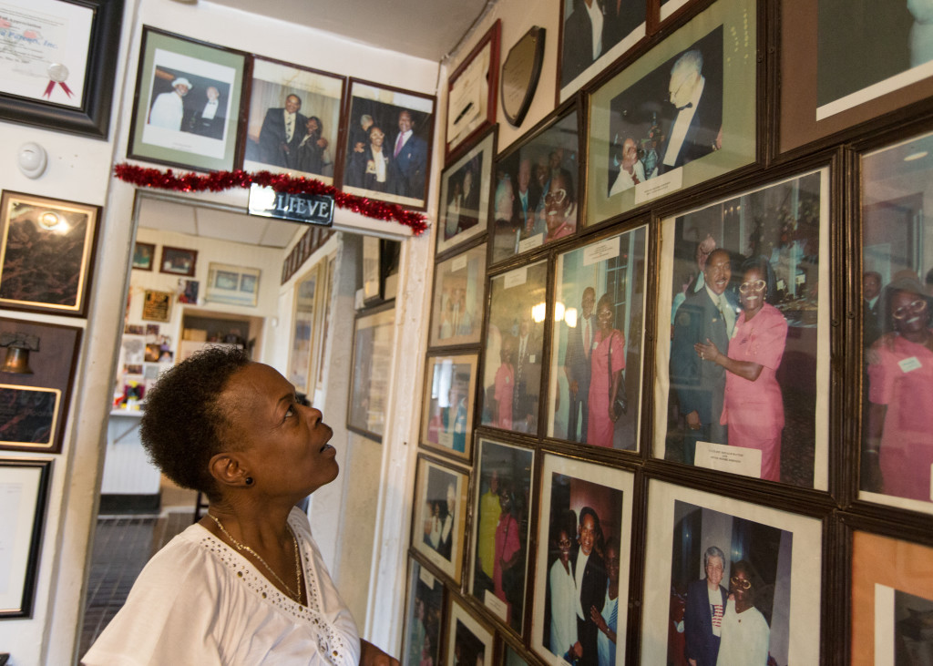 Minnie Moore-Johnson looks up at one of her favorite photos on her office wall, one of her and her mentor Reverend Leon Sullivan. It hangs beside a photo of Moore-Johnson and Bill Clinton.