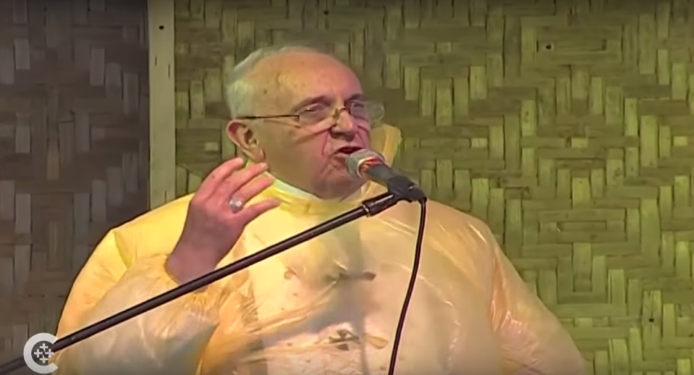 Pope Francis wearing a poncho while delivering mass.