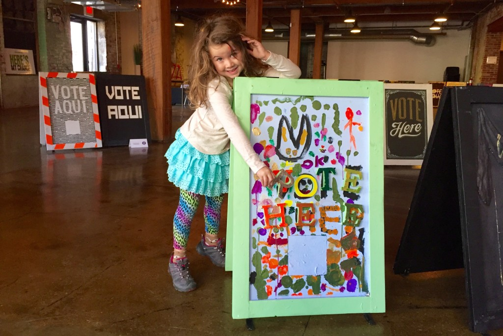 """Olivia Jackson Grant, 5, stands with a """"Vote Here"""" sign she created as part of Next Stop Democracy."""