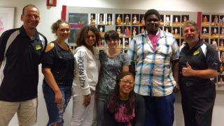 Art Institute student Briana Bailey with others students and members of the Greater Overbrook String Band.