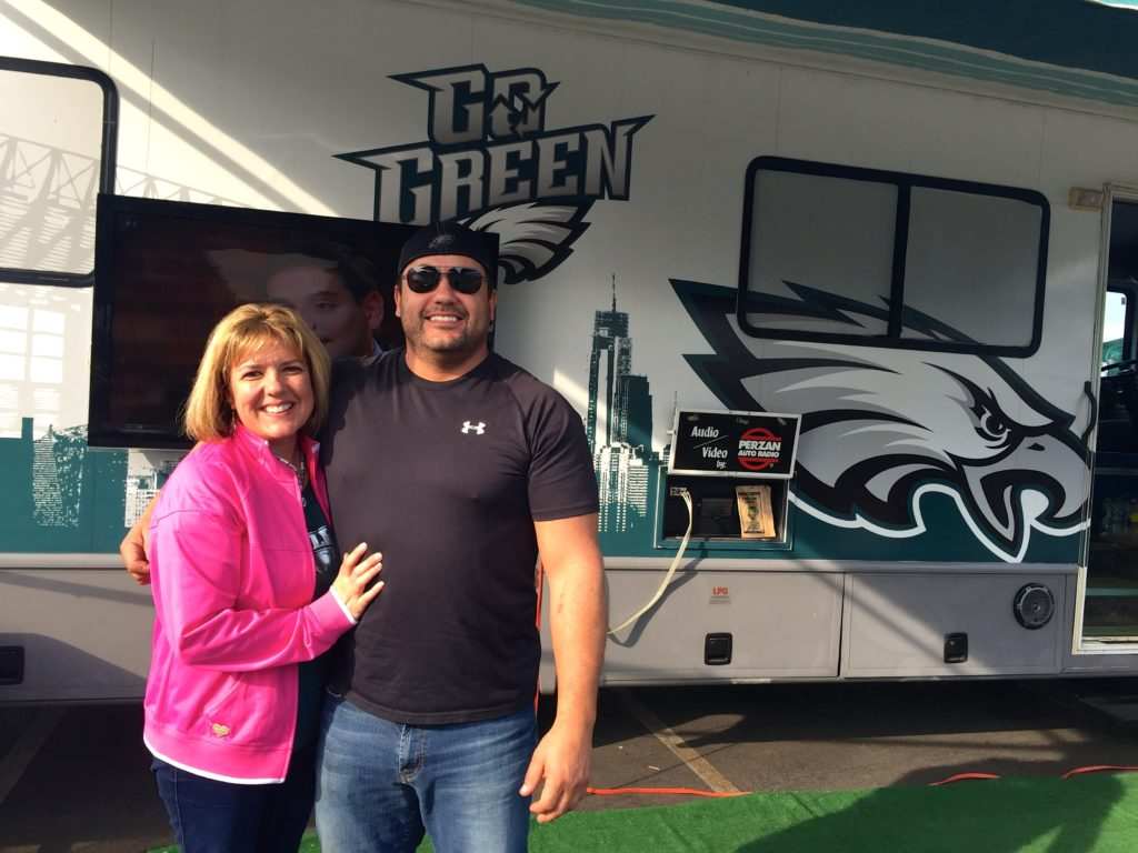Maria Silva and her brother Miguel Ribeiro stand in front of their Eagles tailgate set-up.