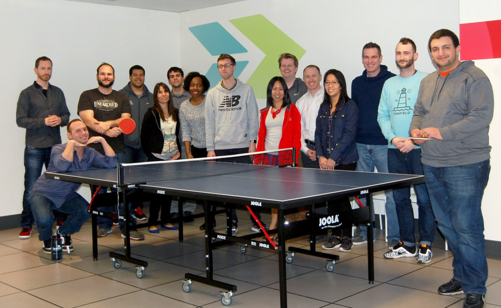 The BrainDo team next to their ping pong table.