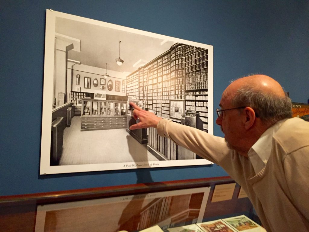 Peter Conn points out a print Inside the exhibit space at The Athenaeum.
