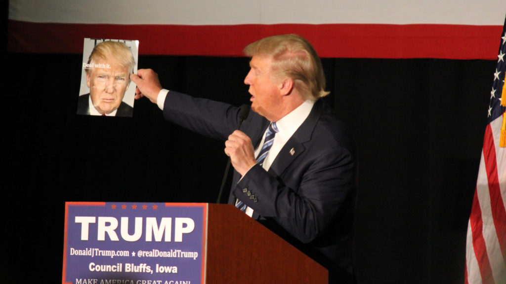 Donald Trump holds up his cover of Time Magazine in Council Bluffs, IA.