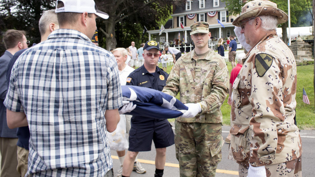 Guest volunteers and veterans helped fold the flag after the ceremony ended.