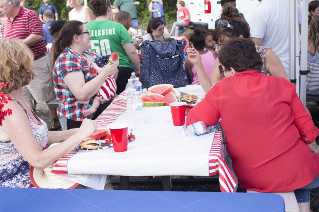 Guests sit under tents while they eat watermelon after the ceremony at the 2016 Memorial Day Event.