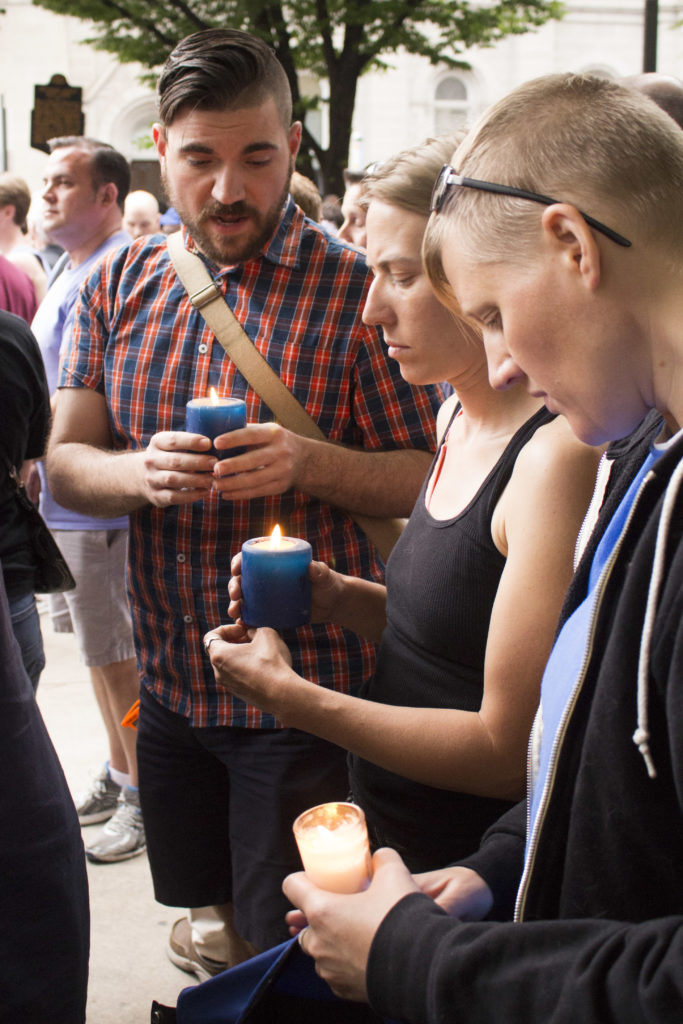 People light candles at a candlelight vigil at City Hall in remembrance of those who died in Orlando.