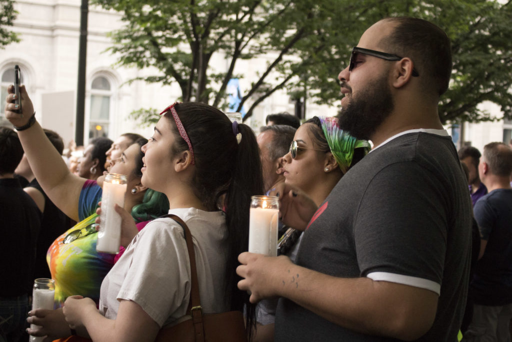 People remained after the ceremony to hold their candles and sing in remembrance of those who died in Orlando.