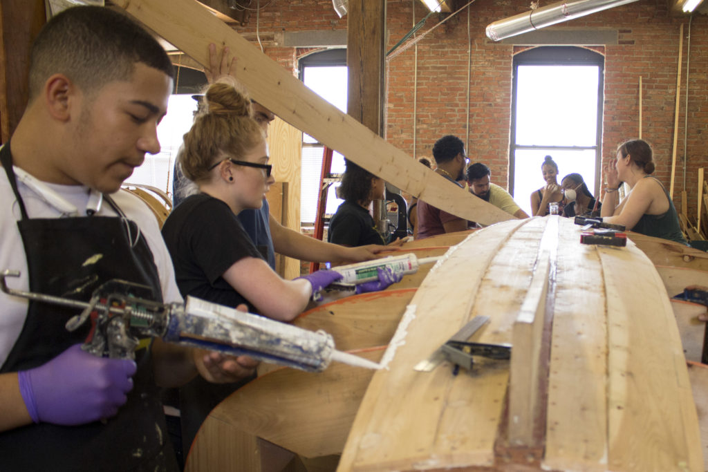 Students work on building a boat at the Philadelphia Wooden Boat Factory in Frankford.
