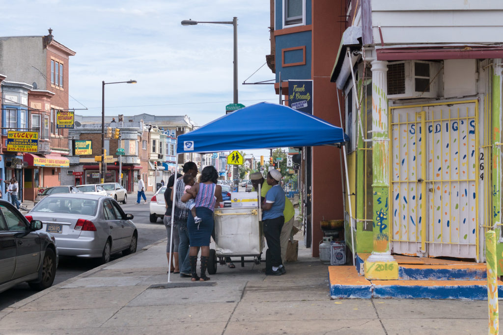 Even though the store's not open yet, the community already congregates at the water ice stand outside