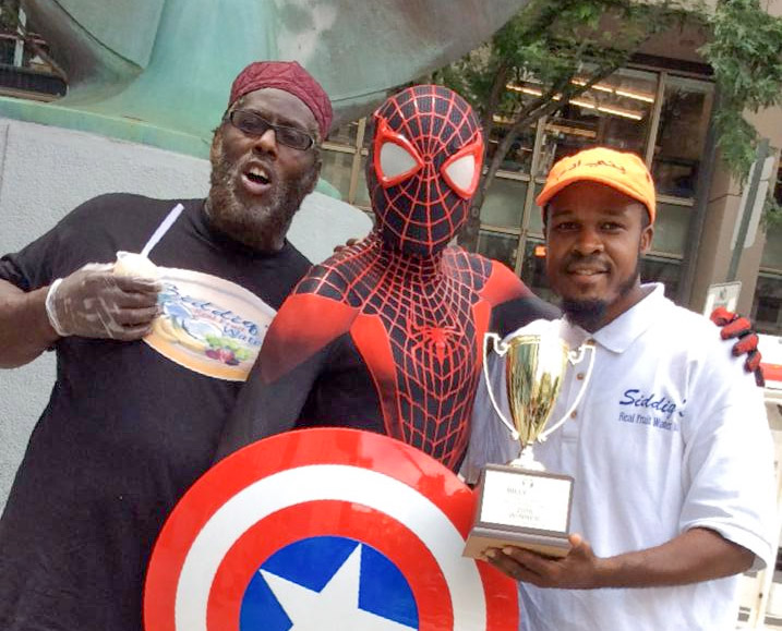 A friend and Spiderman congratulate Moore (right) after he won the Billy Penn Ultimate Frozen Treats Bracket