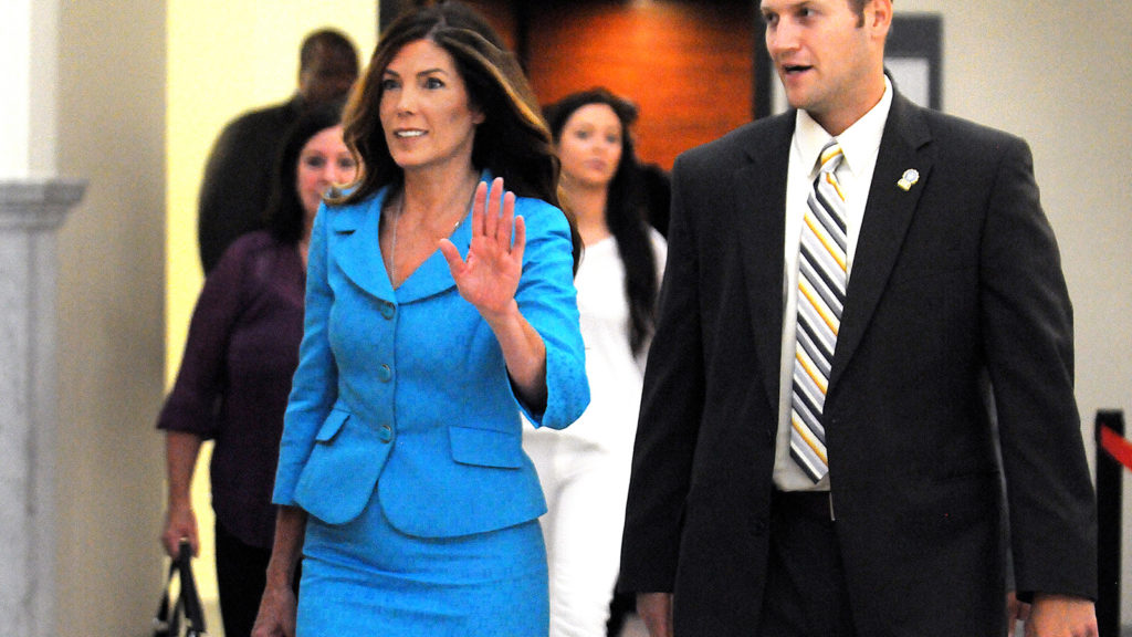 Pa. Attorney General Kathleen Kane waves to onlookers as she enters the Montgomery County courtroom in Norristown.
