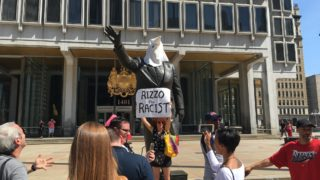 Two protesters placed a KKK hood on the Rizzo statue Friday. Lots of press showed up.