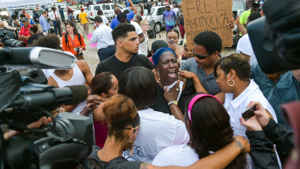 Veda Washington, the aunt of Alton Sterling, is consoled amid protest.