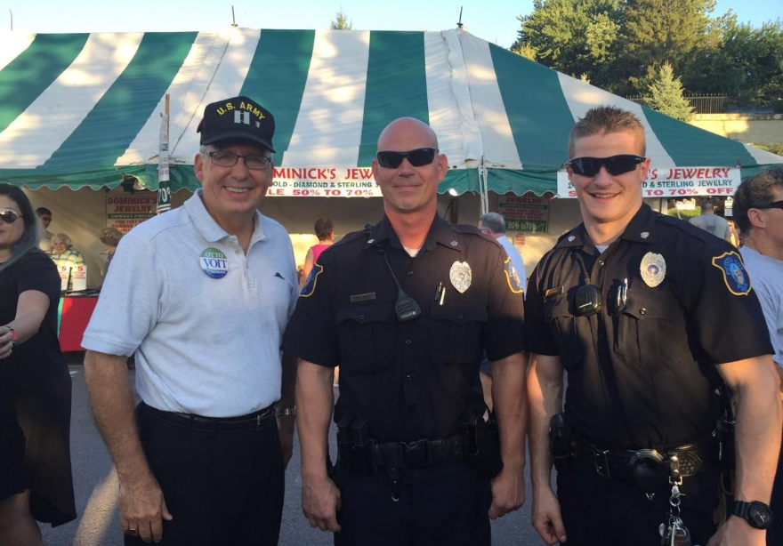 State treasurer candidate Otto Voit, left, poses with officers