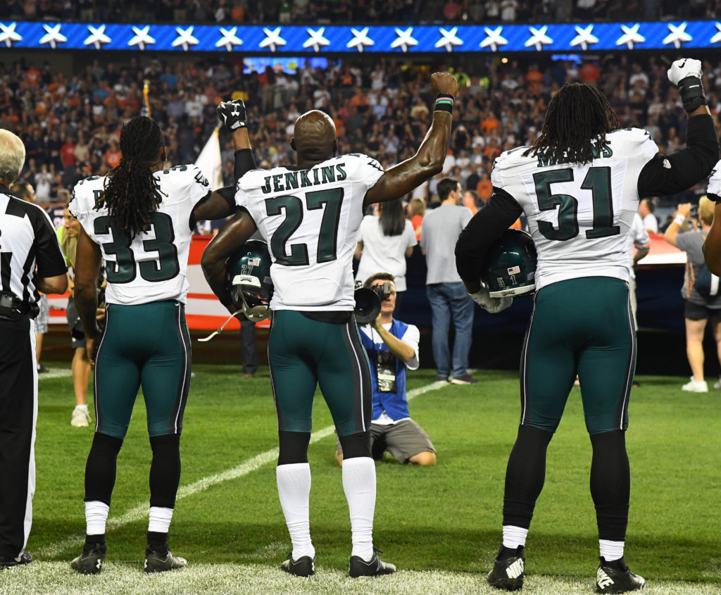 Eagles defensive back Ron Brooks (33), strong safety Malcolm Jenkins (27) and defensive end Steven Means (51) raised their fists during a 2016 game.