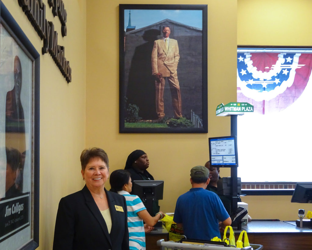 Suzanne Colligas stands in front of the Dr. J print in its new home