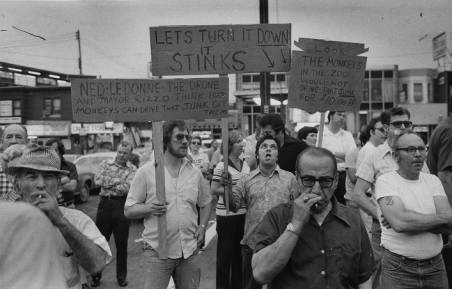 "From the '77 strike: ""Carrying signs which indicate their position on the new contract, workers listen to Donato."""