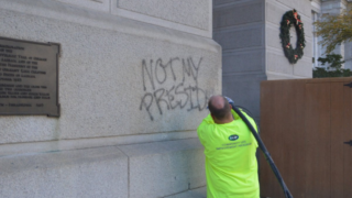 "A city worker cleans graffiti off of Philadelphia City Hall that reads ""Not My President."""
