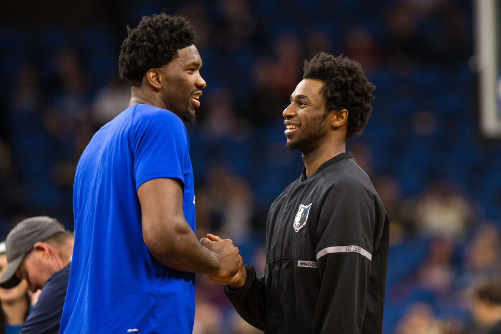 Joel Embiid talks with Timberwolves forward Andrew Wiggins.