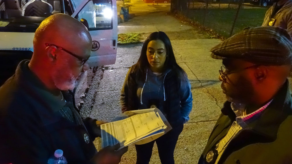 Nuisance Property Unit Chief Tracy Ruffin (right) and inspectors Michael Ross and Aileen Fonseca look over their notes after a visit to the Blue Moon Hotel