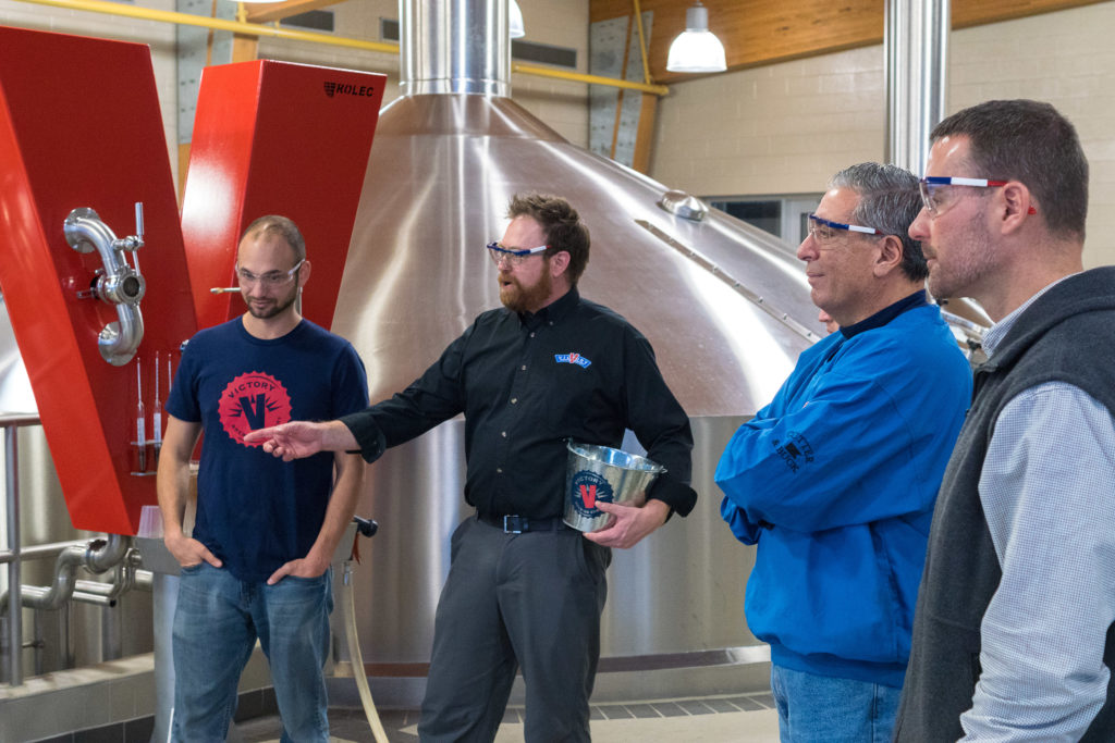 Covaleski explains to Reps. Costa and Harris how breweries make beer