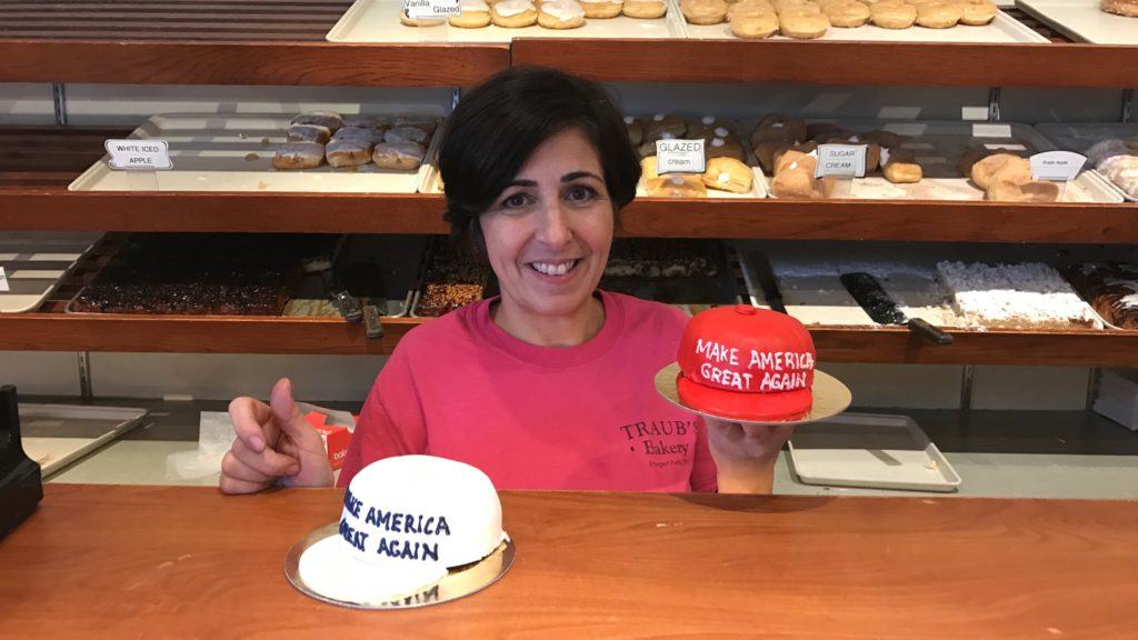 Traub's Bakery Decorator Deneen Ciancaglini stands with her creation, Make America Great Again hat cakes.