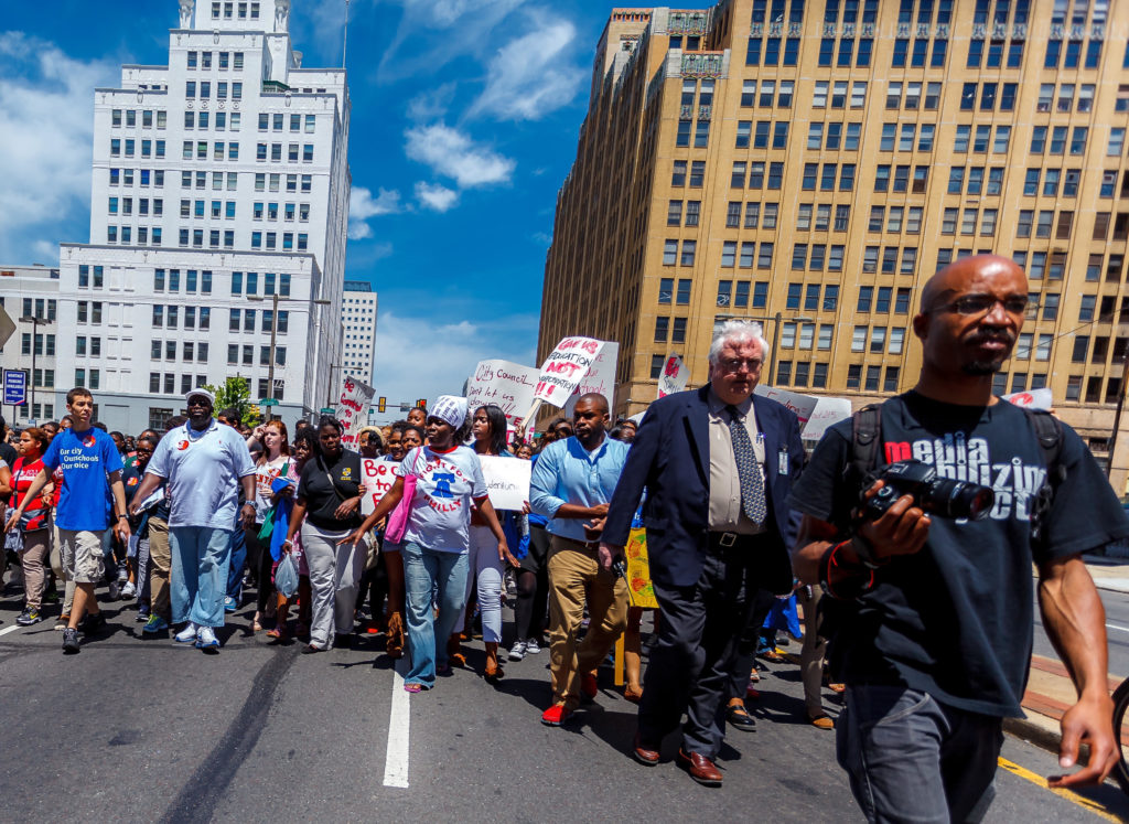 Bryan Mercer, front right, of the Media Mobilizing Project, leads a march.