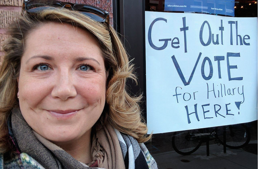 Emily Morse stands with a Get Out the Vote sign.
