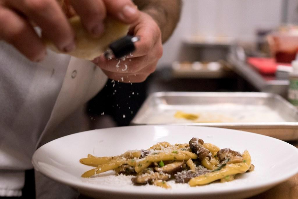 Ferreri grates fresh cheese over a plate of trofie con funghi