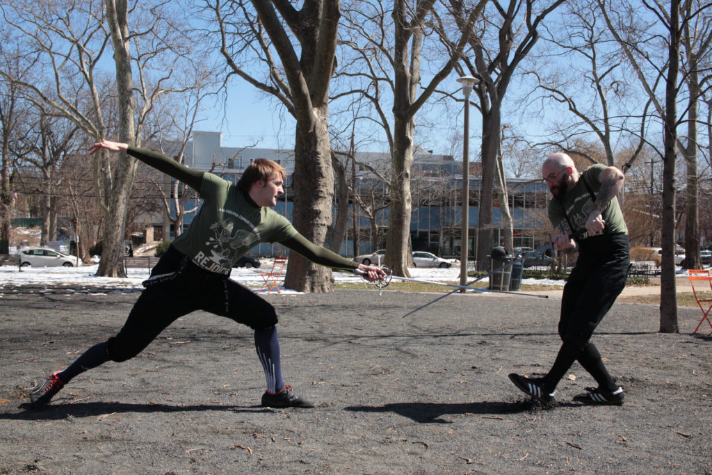 Conner Kemp-Conwell (left) lunges at Graham Meyer (right) with a rapier in a demonstration for the group.