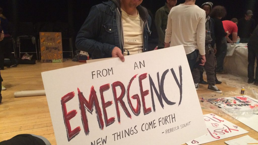 James Cuarcero holds up the banner he made at the Art of Protest workshop at the Kimmel Center.
