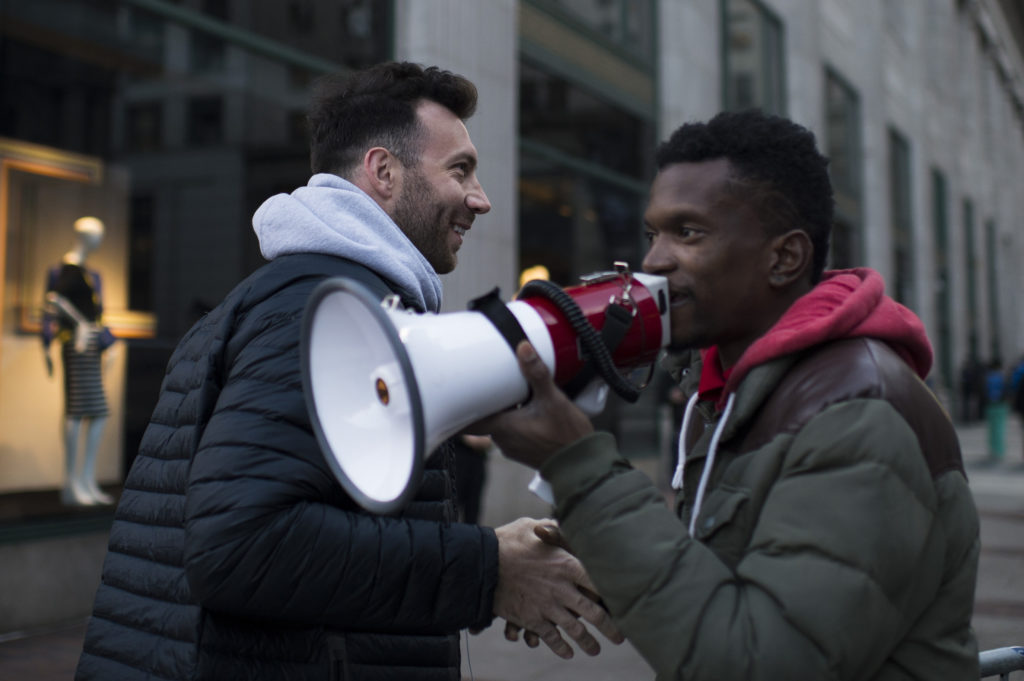 Connor Barwin shakes hands with a protestor as anti-Trump protestors march following a speech from President Trump during a GOP retreat in Philadelphia.