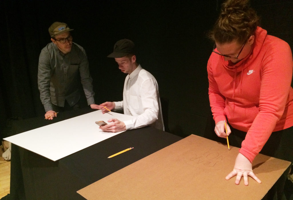 """Alyssa Blank works on her """"Fear not"""" sign at the Art of Protest workshop."""