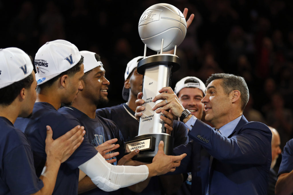 Villanova head coach Jay Wright hands the championship trophy to his players after winning the Big East Conference Tournament final.
