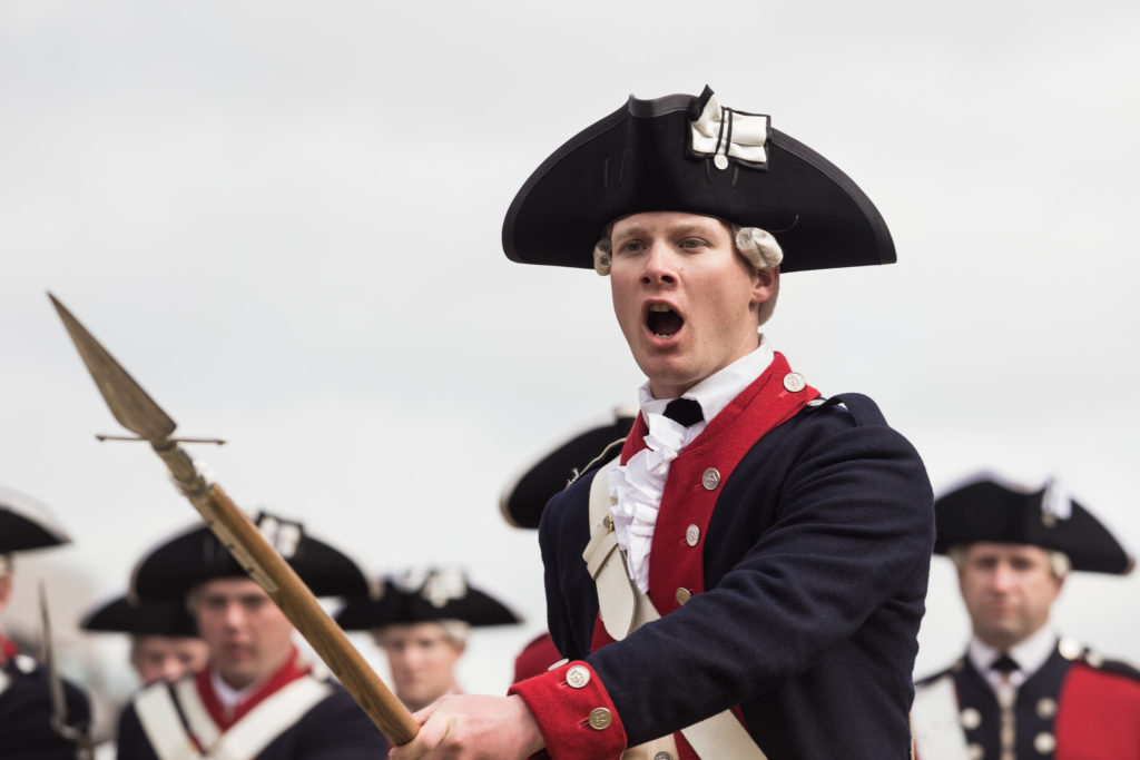 A Revolutionary War re-enactor demonstrates a charge drill at the opening of the Museum of the American Revolution