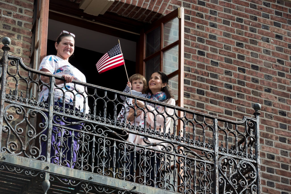 A family across the street from the Museum of the American Revolution watches the opening celebration from a balcony.