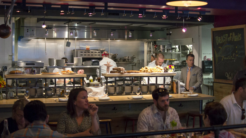 The loud open kitchen at Amis is part of its charm