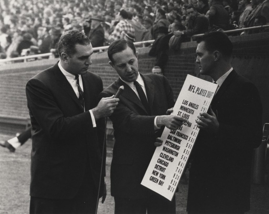 NFL commissioner Pete Rozelle explaining the 1962 NFL draft sequence to CBS commentators Pat Summerall and George Connor.