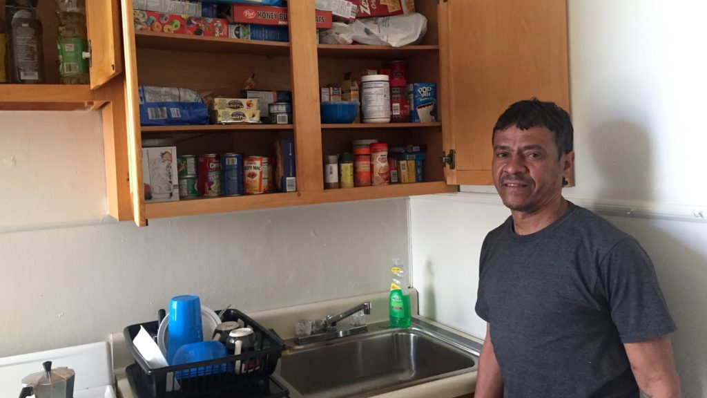 Edgar Figueroa stands in his Pathways-provided apartment with a stocked cabinet.