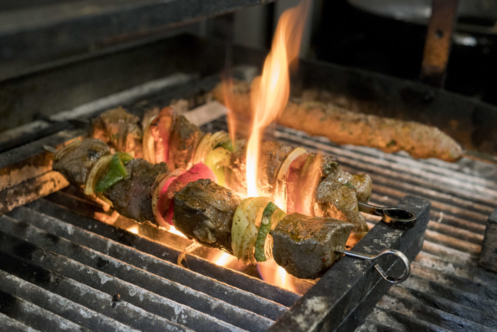 Kebabs cook over an open flame