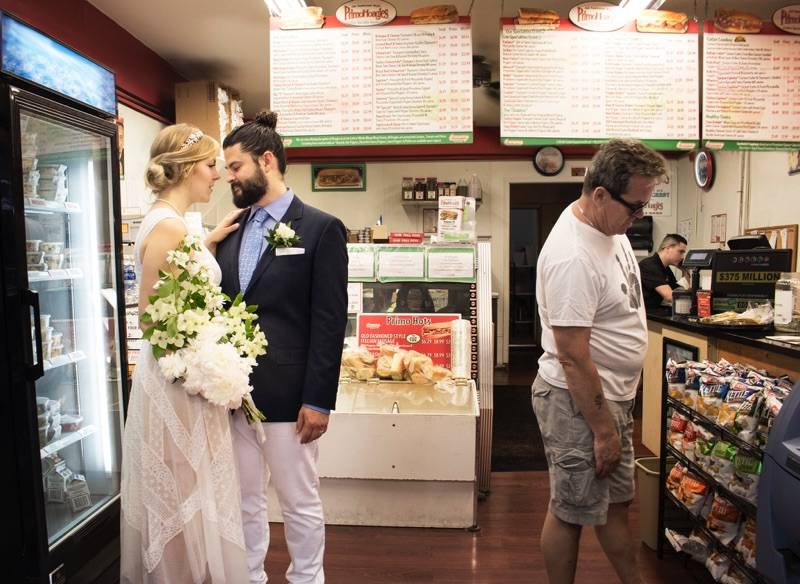Bride Sarah Young and groom John Dubitsky taking a wedding photo at Primo Hoagies in Fishtown.