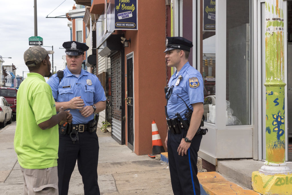 Moore talks with a couple of West Philly foot patrol officers, who are big fans