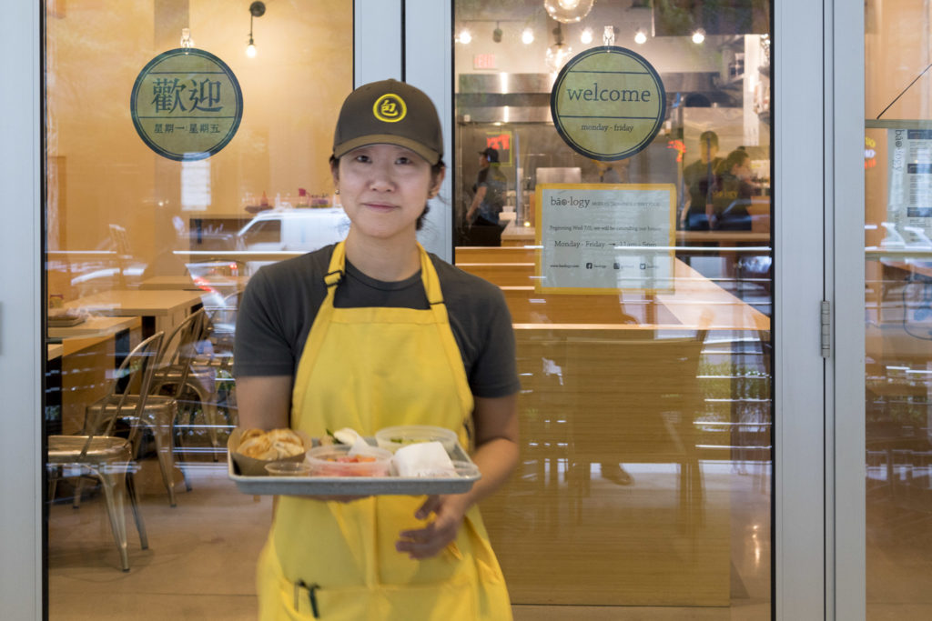 Judy Ni takes a tray of food to the outdoor seats at Baology