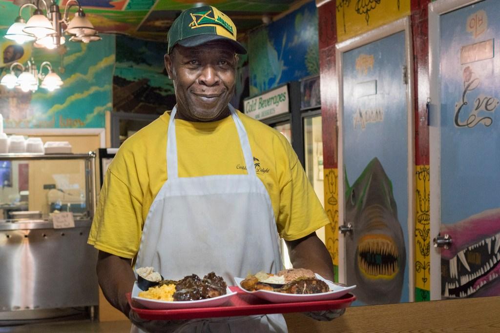 Chef-owner Perceval Cruckshank holds jerk chicken and jerk salmon platters at Caribbean Delight