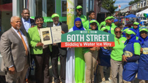 Elected officials present Siddiq Moore and crew with the first of several new signs destined for 60th Street
