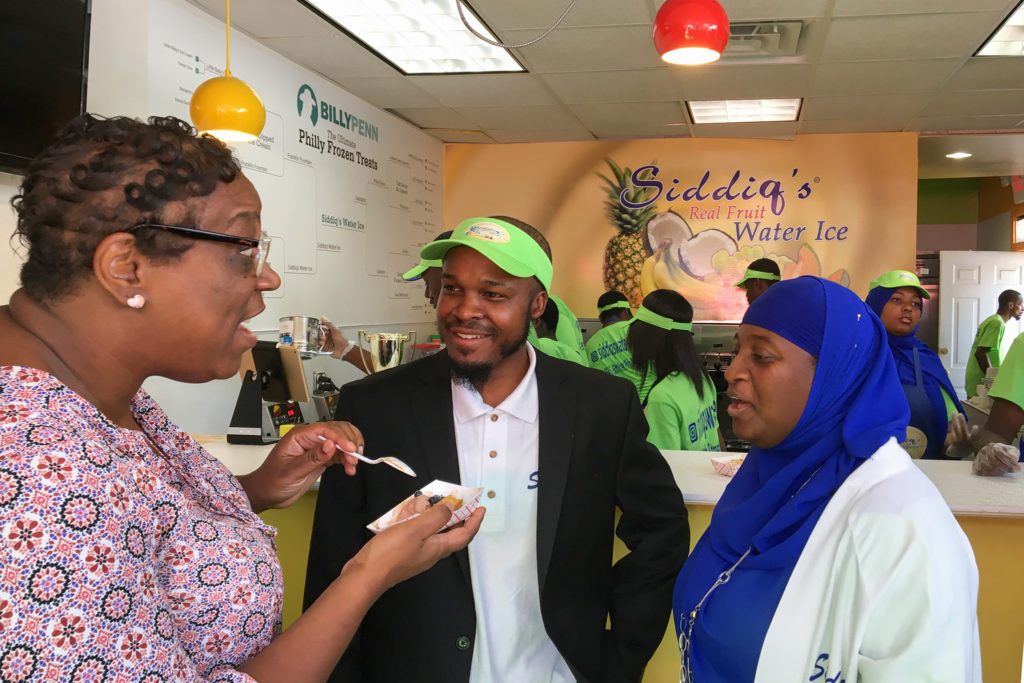 Neighbor Michelle talks with Siddiq Moore and his wife inside the new store