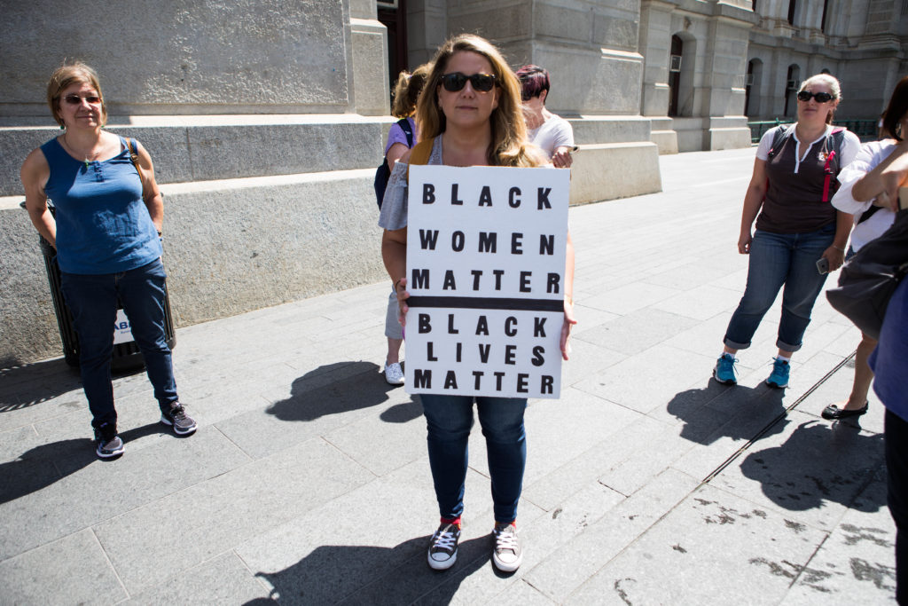 """Emily Cooper Morse, a 34-year-old from Philly suburb, King of Prussia, holds a sign reading """"Black Women Matter, Black Lives Matter"""". Cooper Morse is the founder and organizer of Philly's Women's March that took place earlier this year."""