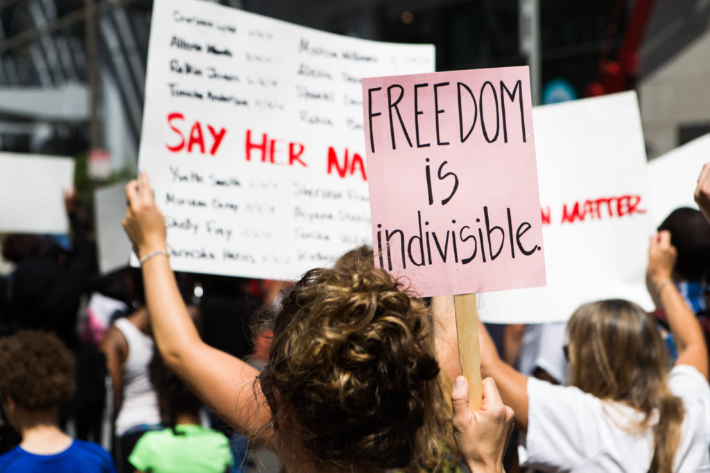 """A march participant holds a sign bearing the words """"Freedom Is Indivisible"""" while making her way up Broad Street with the rest of the participants earlier this afternoon."""