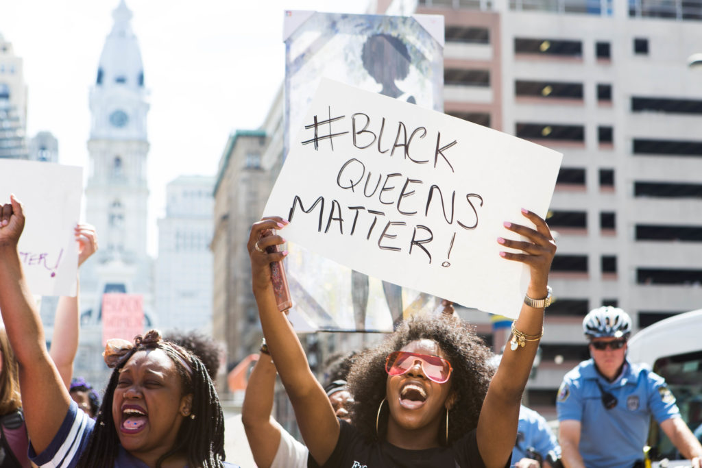 """A march participant chats along with the rest of the crowd, holding a sign bearing the words """"#BLACK QUEENS MATTER"""" while making her way up Broad Street with the rest of the crowd earlier this afternoon."""